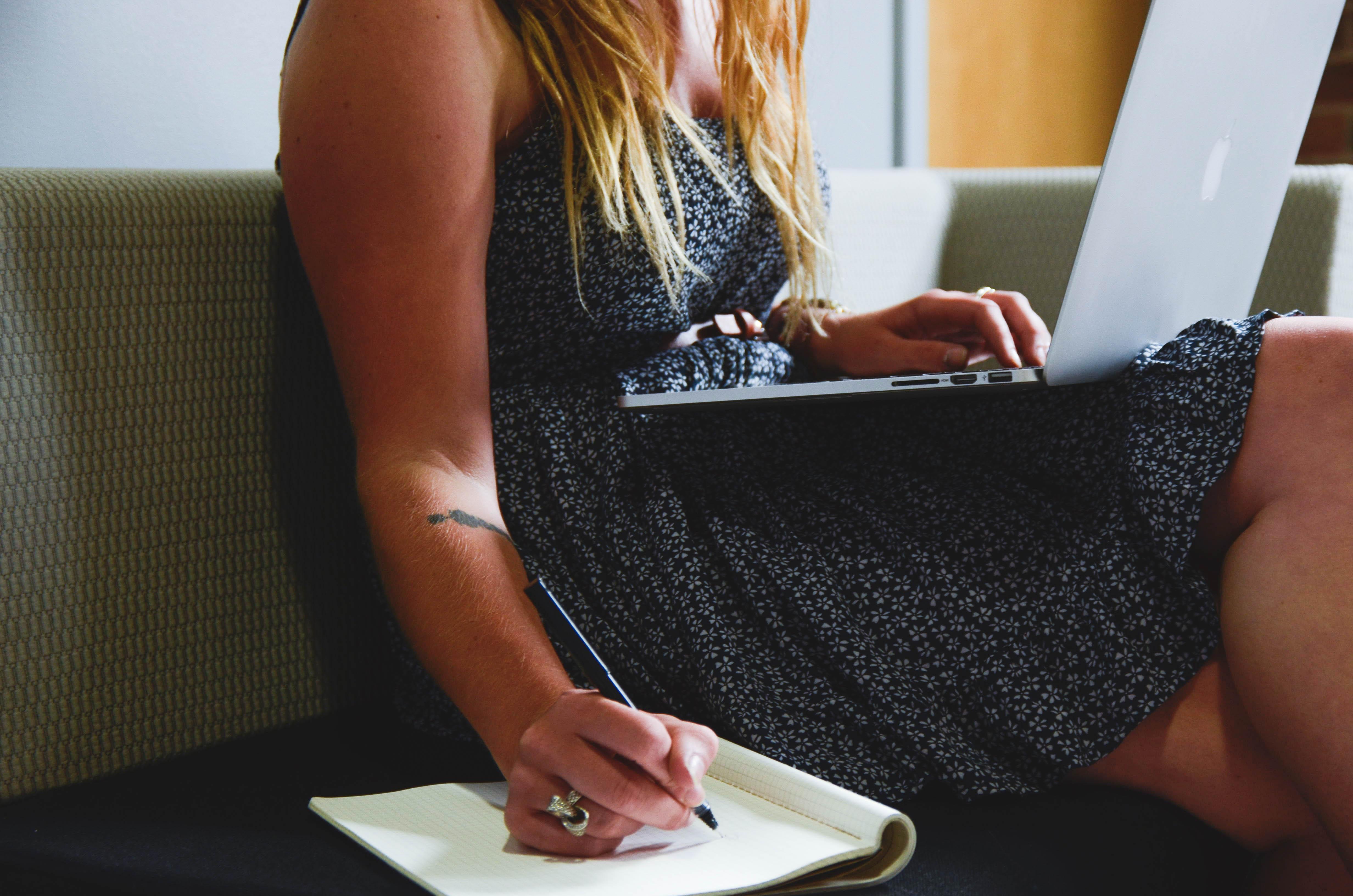 Žena, ktorá pozerá do notebooku a píše si poznámky