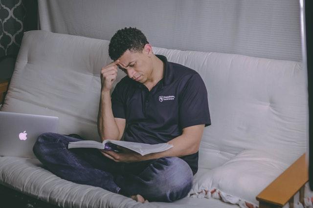 Muž s notebookom premýšľajúci nad knihou