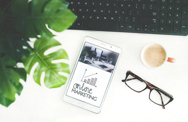 """Pracovný stôl, na ktorom je mobil s nápisom """"Online marketing"""""""