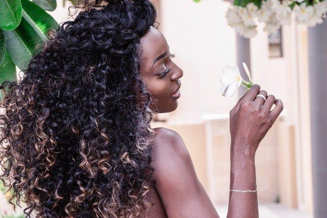 Černoška s dlhými kučeravými vlasmi, ktorá privoniava ku kvetu