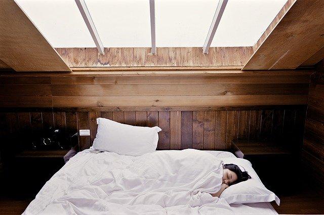 Žena ležiaca v posteli v podkrovnej spálni