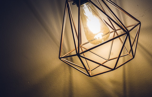 Zapálená žiarovka v kovovom tienidle od lampy.jpg