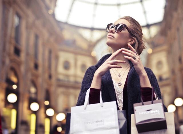 Žena v obchodnom centre so slnečnými okuliarmi a šperkmi na krku a prstoch