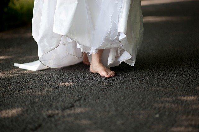 Žena v svadobných šatách kráča bosá po betóne.jpg