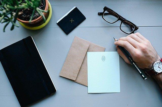 Muž sedí pri stole má pred sebou papier obálku a v ruke drží pero.jpg