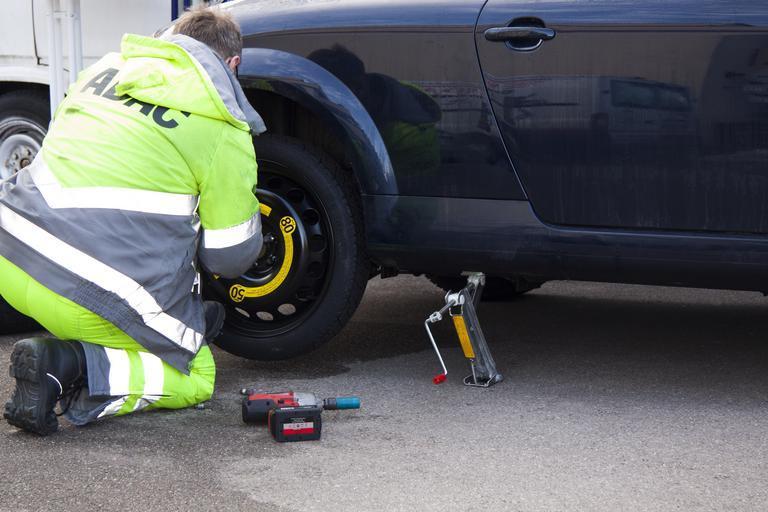 Muž opravuje koleso na aute.jpg