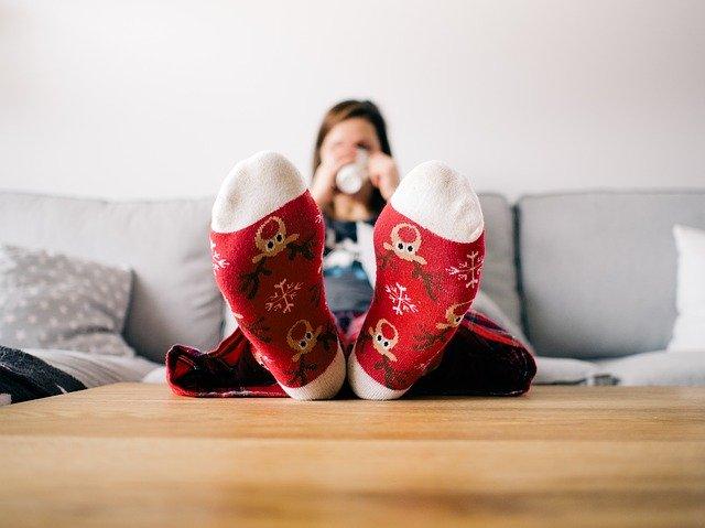 Žena v červených ponožkách so sobmi má vyložené nohy na stole a pije zo šálky.jpg