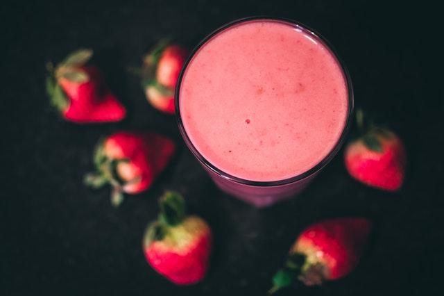 Červené smoothie v pohári a jahody na stole.jpg