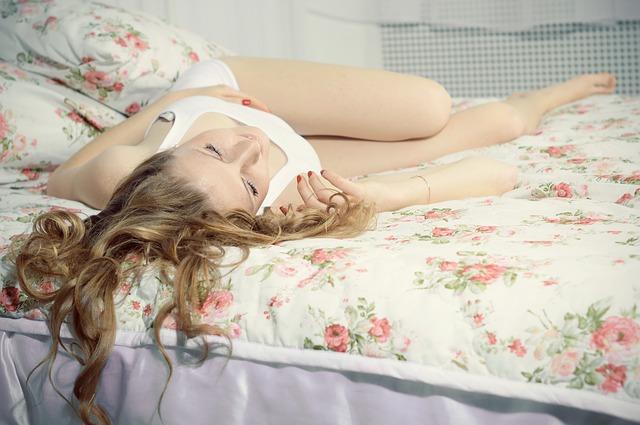 Žena s dlhými vlasmi, v bielom tielku s výstrihom leží blažene na posteli.jpg