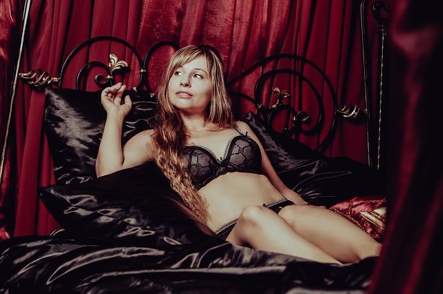 Žena v čiernej podprsenke leží na posteli so zamatovými čiernymi vankúšmi.jpg