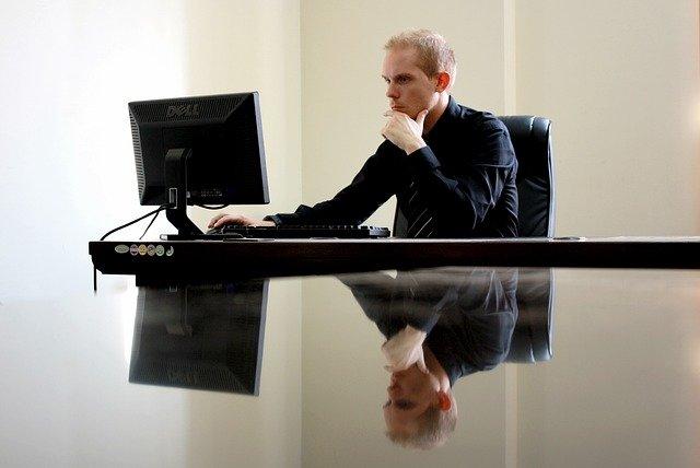 Zamyslený muž v čiernej košeli sedí pri stole a pozerá do počítača