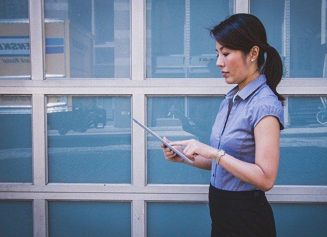 Žena de popri sklenenej budove a pozerá do tabletu
